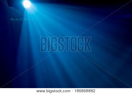 The rays of searchlights in smoke on stage during a performance