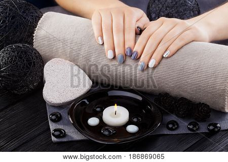 beautiful gray manicure with oil, candles and towel on the white wooden table. spa