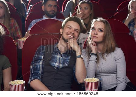 Front view of serious blonde woman and smiling brunet man watching movie in modern cinema hall, looking at screen. Two best friends spending time together, thinking, dreaming when watching film. Popcorn in cinema.