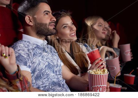 Side view of beautiful couple of caucasian girlfriend and arabian boyfriend watching interesting film at cinema hall, eating popcorn and drinking cola. Happy friends thinking about movie and smiling.