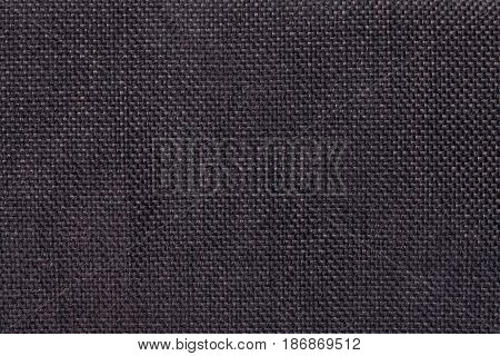 Dark brown woolen background of dense woven bagging fabric closeup. Structure of the black cloth with natural texture. Cloth backdrop.