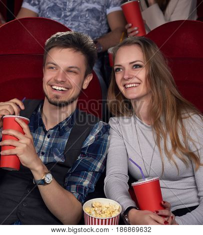 Emotionally happy couple of young and beautiful girlfriend with long hair and boyfriend in checked shirt watching new comedy movie at modern cinema. Two friend eating popcorn, drinking cola at cinema.