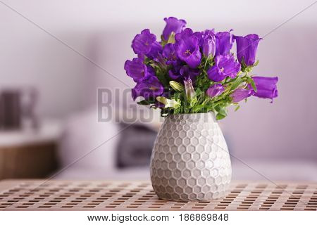 Bouquet of purple bellflowers in vase on wooden table
