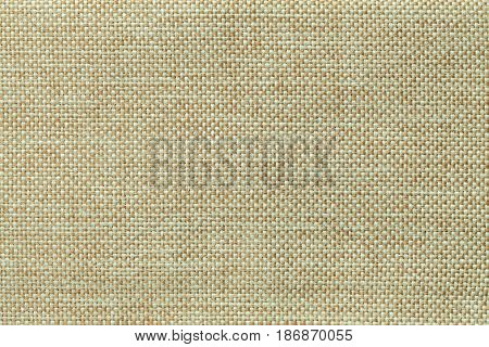 Light green woolen background of dense woven bagging fabric closeup. Structure of the olive cloth with natural texture. Cloth backdrop.