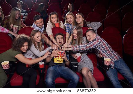 Positive and emotional group of young women and men angry and wanting eating, pulling hands to popcorn to one of boy in center, who screaming. Man holding big bucket with tasty popcorn at cinema.