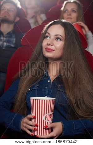 Portrait of beautiful brunette woman with long hair and bright make up, red lips watching interested movie at cinema. Young girl sitting alone, holding popcorn, watching at projector at cinema hall.