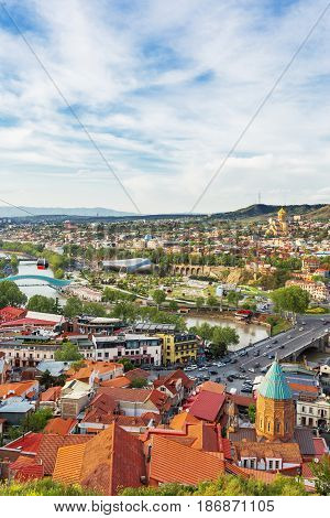 Panorama view of Tbilisi capital of Georgia country. Perestrian Bridge of Peace over Kura river. Cable road over the city. The Holy Trinity Cathedral of Tbilisi (commonly known as Sameba) and Presidential Administration of Georgia.