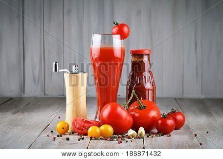 Still life with fresh tomatoes, garlic, tomato juice and tomato sauce on wooden boards.
