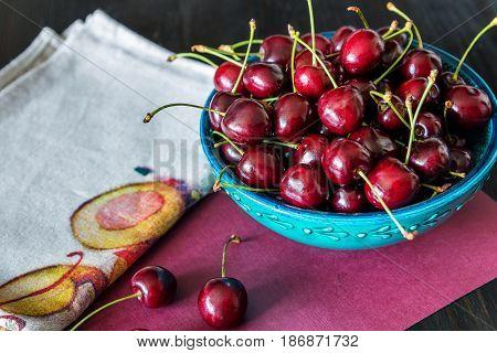 red cherries in green ceramic bowl on dark background