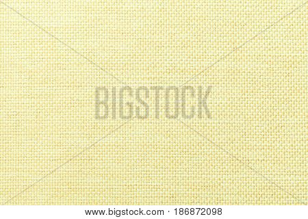 Light yellow woolen background of dense woven bagging fabric closeup. Structure of the lemon color cloth with natural texture. Cloth backdrop.