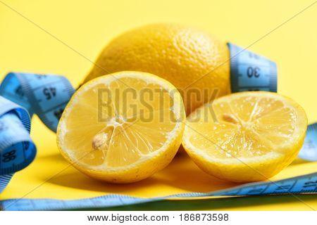 Fitness Concept. Centimeter With Lemon Or Orange Fruit On Yellow