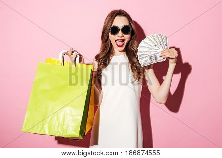 Image of a smiling young brunette woman in white summer dress holding money posing with shopping bags and looking at camera over pink background.