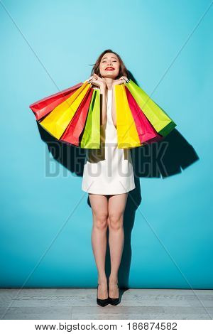 Full length portrait of a happy satisfied girl holding colorful shopping bags isolated over blue background
