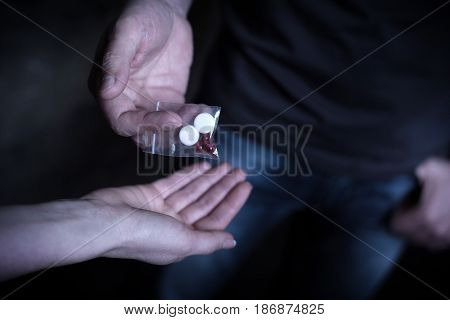 Incredibly dependent from drugs. Obsessive stoned drug addicted people holding packet with cocaine pills while sharing drug and getting dope dose