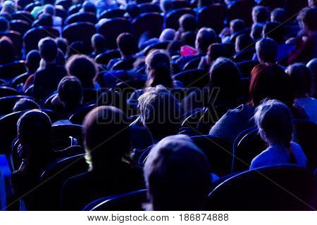 People, children, adults, parents in the theater watching the performance.