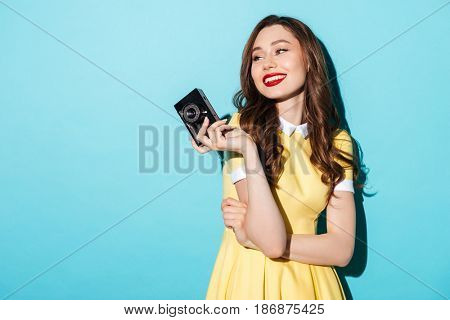 Portrait of a smiling beautiful woman in dress holding vintage camera and looking away isolated over blue background