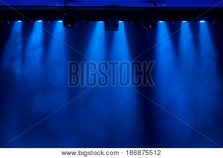 The blue light from the spotlights through the smoke in the theatre during the performance. Lighting equipment.