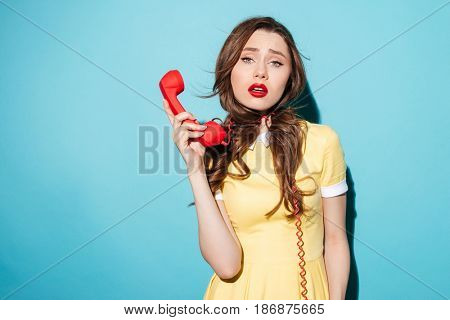 Portrait of a tired exhausted woman with telephone cord around her neck holding tube and looking at camera isolated over blue background