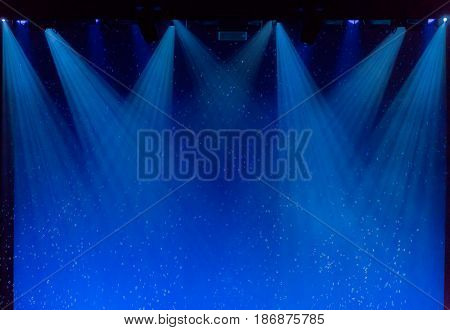 Bubbles and rays of blue light through the smoke on stage during theatrical performances.
