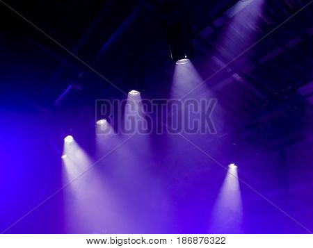 The light rays from the spotlight through the smoke. Lighting equipment on the ceiling. The stage of a theatre or night club. Show or performance.