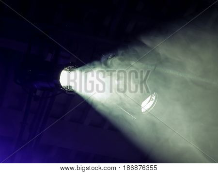 The beam from a searchlight through smoke. Lighting equipment on the ceiling. The stage of a theatre or night club. Show or performance.