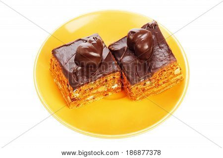 Two chocolate cakes on orange plate isolated on a white background