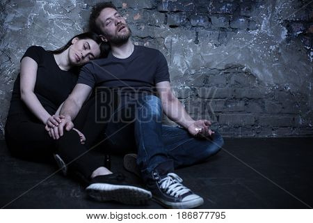 Nobody understands us. Hopeless tired cocaine addicted couple holding cocaine pills while feeling useless and suffering from delusions