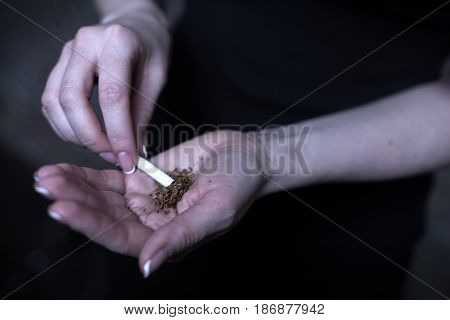 Everyday dangerous addiction. Obsessive young drug addicted woman holding marijuana cigarette while using drug and getting new dose