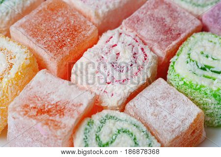 Assorted colorful Turkish Delight as background. Set of assorted traditional eastern desserts. Arabian sweets on a metal dish. rahat lokum in a colorful plates. Selective focus