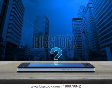 Question mark icon on modern smart phone screen on wooden table over office city tower Customer support concept