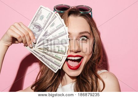 Image of a happy young brunette lady in white summer dress holding money and looking at camera over pink background.