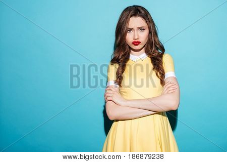 Portrait of a cute upset girl in dress standing with arms folded and looking at camera isolated over blue background