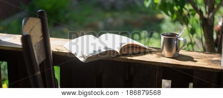 Metal mug, book and chair on the wooden terrace