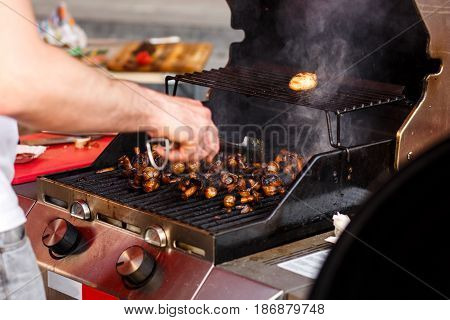 Man Roasting Mushrooms, Holding Tongs, On Open Grill, Outdoor Kitchen. Chef Making Vegetable Meal, F