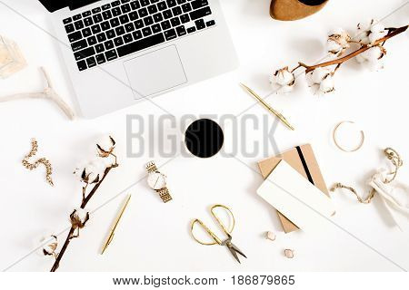 Flat lay fashion blogger gold styled desk with laptop and woman accessory collection and cotton branch on white background. Top view.
