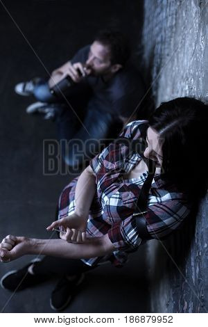 Without willpower at all. Apathetic depressed drug addicted couple sitting in the dark place while drinking alcohol and getting heroin injection