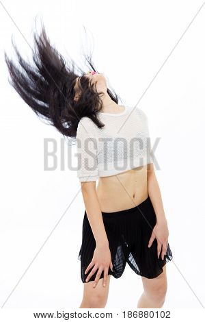 Young Asian teenage girl flinging hair back