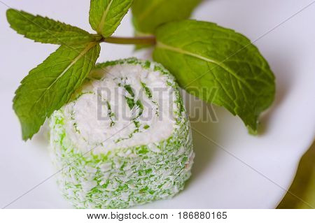 Sweet piece of turkish delight on white background With a leaf of mint
