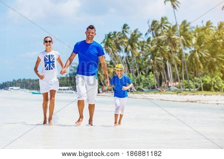 Happy kids with father having fun on tropical beach