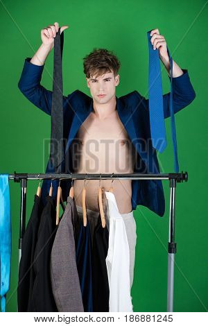 Wardrobe Hanger With Formal Outfit And Shaved Man Choosing Suit