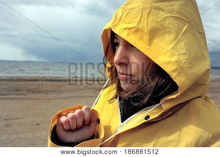 A young girl in a wet yellow raincoat looks at the water of the bay, overhead dark clouds and it rains, a sad and pensive look, a cold spring weather.