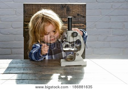 child or student boy with microscope study science at educational workplace makes experiment