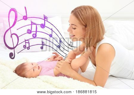 Mother with baby on bed. Lullaby songs and music concept