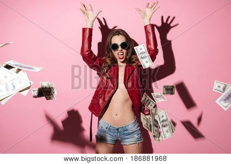 Portrait of a happy screaming woman winner throwing money banknotes isolated over pink