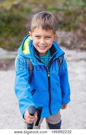 Happy hiking boy with trekking sticks in the mountains. Norway