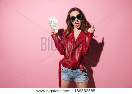 Portrait of a rude crazy girl in leather jacket holding money banknotes and showing middle finger gesture isolated over pink