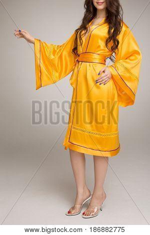 Girl in yellow silk robe, on gray background