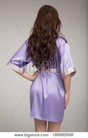 Girl in lilac silk robe, gray background