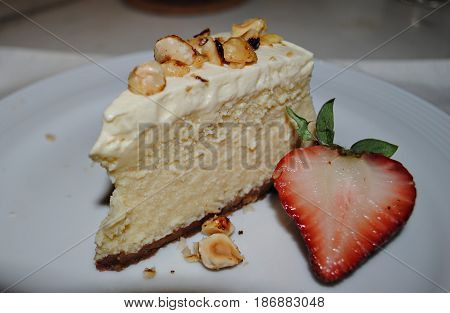 slice of cheesecake with strawberry and walnuts A slice of tempting cheesecake topped with walnuts and served with half a slice of strawberry.