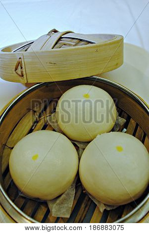 Siopao or steamed buns in a bamboo steamer Siopao is a popular food in southeast Asia usually filled with meat and steamed.